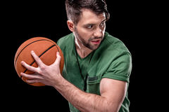 Portrait of concentrated man holding basketball ball and looking away Royalty Free Stock Images