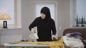 Portrait of concentrated muslim woman in hijab ironing yellow pullover. Housewife doing housework indoors. Patriarchal
