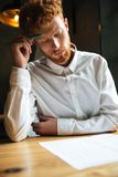 Portrait of concentrated readhead curly bearded man, reading pap Royalty Free Stock Photos