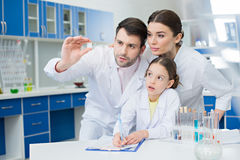 Portrait of concentrated scientists looking at microscope slide Stock Image