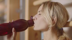 Portrait of concentrated woman having break after sport exercise. Relaxed sport woman drinking water in fitness gym. Portrait of concentrated woman having break stock footage
