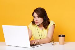 Portrait of concentrated woman manager sitting at table with laptop on yellow background in studio, lady looks astonished on. Screen of computer, has problems stock photos