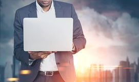African American man with laptop in a blurred city Royalty Free Stock Photography