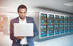 African American man, laptop server room polygons. Portrait of a concentrated young African American businessman wearing a suit and looking attentively at his Royalty Free Stock Photography