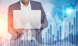 African American man laptop, graphs in a city Royalty Free Stock Images