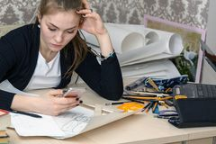 Portrait of a concentrated young student at the table is engaged in drawing architectural design, drawing, sketch, geometry, model.  Royalty Free Stock Photos
