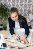 Portrait of a concentrated young student at the table is engaged in drawing architectural design, drawing, sketch, geometry, model.  Stock Images
