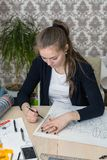 Portrait of a concentrated young student at the table is engaged in drawing architectural design, drawing, sketch, geometry, model.  Royalty Free Stock Photography