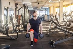 Portrait of concentration young adult man handsome athlete working out in gym, standing on the knees and holding two dumbbells,. Doing exercises for legs and stock image