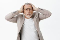 Portrait of concerned and troubled shocked senior man with white hair and beard in suit and glasses holding hands on. Head anxiously feeling worried learning stock photography