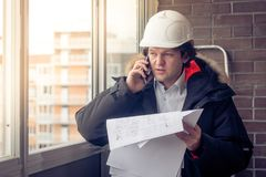 Portrait of concerned unshaven builder telling by mobile while keeping different projects in hand. Communication and royalty free stock images