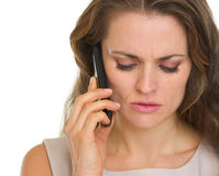 Portrait of concerned woman talking mobile phone. Isolated on white Stock Photo