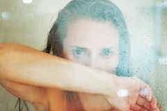 Portrait of concerned young woman behind shower door Royalty Free Stock Image