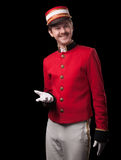 Portrait of a concierge (porter). In a red jacket on a black background. Isolated on black Royalty Free Stock Images