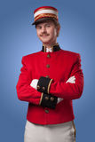 Portrait of a concierge (porter). In a red jacket on a blue background royalty free stock photo