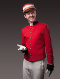 Portrait of a concierge (porter). In a red jacket on a gray background Royalty Free Stock Images