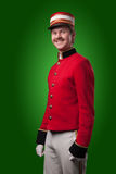 Portrait of a concierge (porter). In a red jacket on a green background Stock Photo