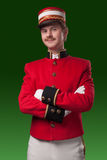 Portrait of a concierge (porter). In a red jacket on a green background Stock Photos