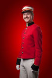 Portrait of a concierge (porter). In a red jacket on a red background Stock Photography