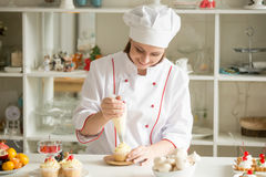 Portrait of confectioner topping a cupcake with cream Royalty Free Stock Photography