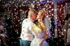 Portrait of confetti flying at dancing beautiful bride and groom Royalty Free Stock Photos