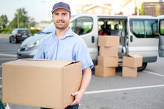 Portrait of confidence express courier and delivery van. Portrait of confidence express courier next to his delivery van royalty free stock images