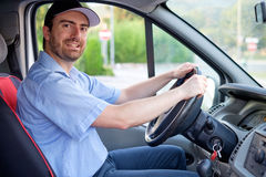 Portrait of confidence express courier. Driving his delivery van stock photography