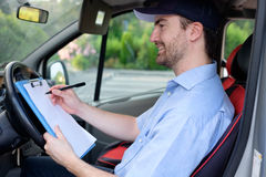 Portrait of confidence express courier. On his delivery van royalty free stock photo