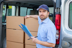 Portrait of confidence express courier. Next to his delivery van royalty free stock photo