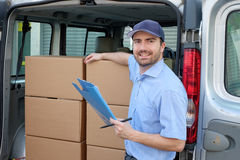 Portrait of confidence express courier next to his delivery van. Man stock photography