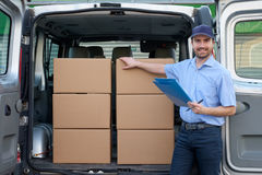 Portrait of confidence express courier next to his delivery van Stock Photo