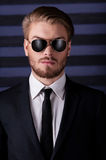 Portrait of confidence and masculinity. Portrait of handsome young man in sunglasses and formalwear looking at camera while standing against striped background Stock Photo