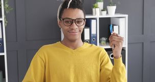 Confident businessman holding a pen at office. Portrait of confident african american businessman holding a pen while sitting at office chair stock footage