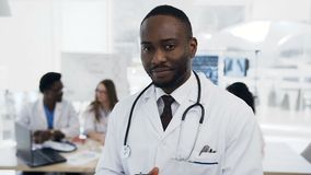 Portrait of confident african doctor looking to the camera with team of cowoker on the background in hospital.