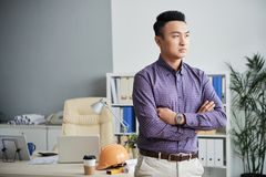 Ambitious engineer. Portrait of confident ambitious engineer standing with his arms crosses royalty free stock image