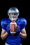 Portrait of confident American football player holding ball Stock Photos