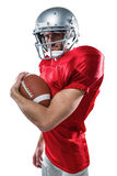 Portrait of confident American football player in red jersey holding ball. On white background Royalty Free Stock Photos