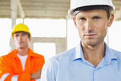 Portrait of confident architect at construction site with coworker in background Royalty Free Stock Image