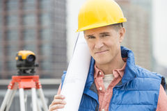 Portrait Of Confident Architect Holding Rolled Up Blueprint Stock Photos