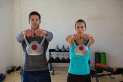 Portrait of confident athletes lifting kettlebells. In health club Royalty Free Stock Images