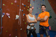 Portrait of confident athletes standing by climbing wall in gym Royalty Free Stock Photos