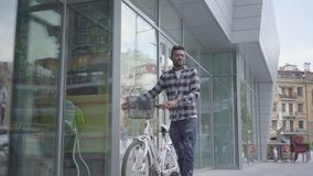 Portrait confident attractive African American man standing with bicycle against the background of urban architecture. Handsome African American man standing stock footage