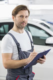 Portrait of confident automobile mechanic writing on clipboard in workshop Royalty Free Stock Photos