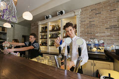 Portrait of confident bartender at counter with coworkers in background Stock Photography
