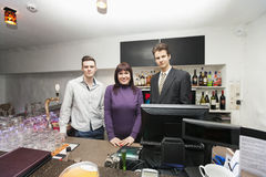 Portrait of confident bartenders and manager at bar counter Royalty Free Stock Image