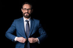 Portrait of confident bearded middle aged businessman in eyeglasses buttoning suit jacket Royalty Free Stock Image