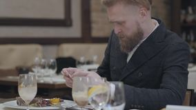 Portrait confident blond bearded man in stylish jacket taking a photo of his food with his cellphone sitting in a modern. Confident blond bearded man in stylish stock video