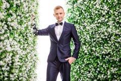 Portrait of confident bridegroom standing amidst flower decorations Stock Photography