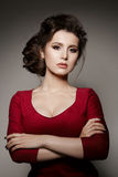 Portrait of confident brunette girl posing with crossed arms at camera. Gorgeous woman wearing in red dress with perfect haircut a Royalty Free Stock Photography