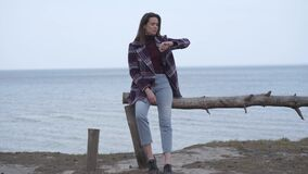 Portrait of confident brunette woman checking time on watch as sitting on log on riverbank. Beautiful Caucasian girl
